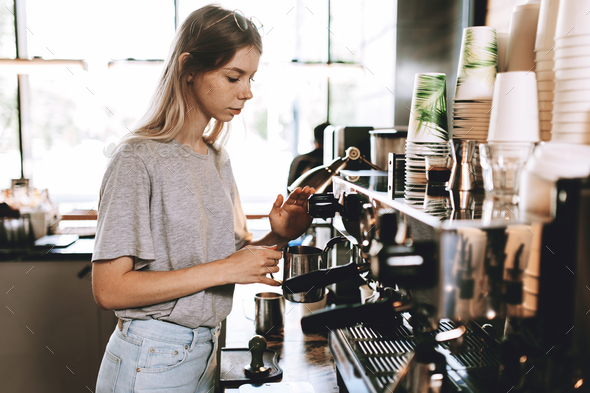 A young pretty thin blonde,dressed in casual outfit,is cooking coffee in a popular coffee shop - Stock Photo - Images