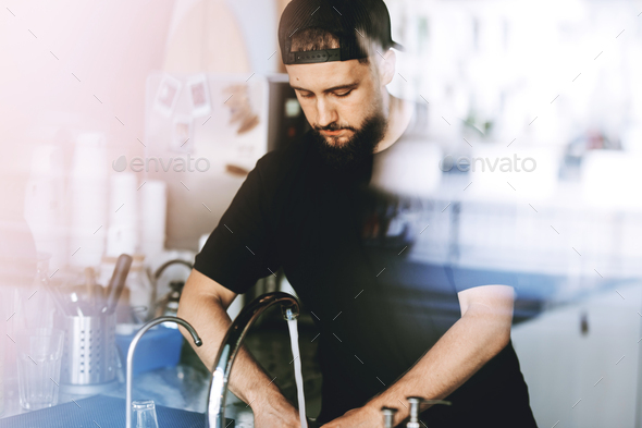 A youthful stylish young man with beard,wearing casual clothes,is washing glasses in a cozy coffee - Stock Photo - Images