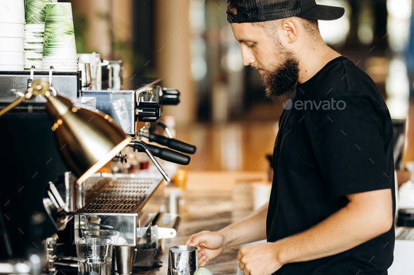 A stylish young man with beard,wearing casual clothes,cooks coffee in a coffee machine in a modern - Stock Photo - Images