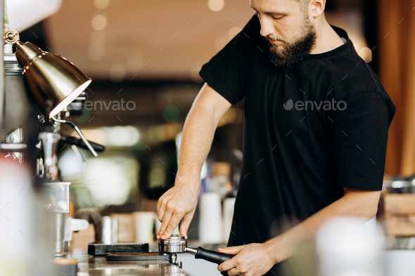A stylish young man with beard,wearing casual clothes,cooks coffee in a coffee machine in a cozy - Stock Photo - Images