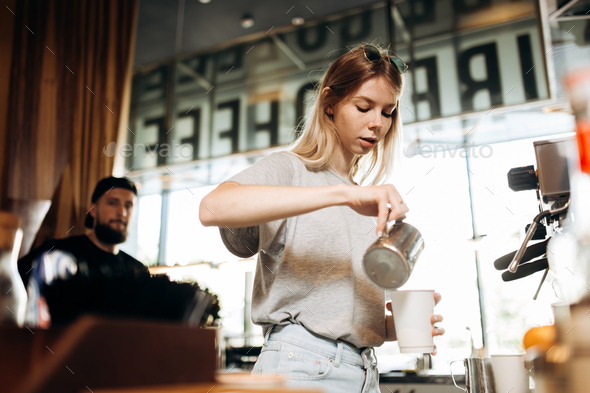 A youthful thin blonde girl,wearing casual cothes,is shown adding milk to the coffee in a cozy - Stock Photo - Images