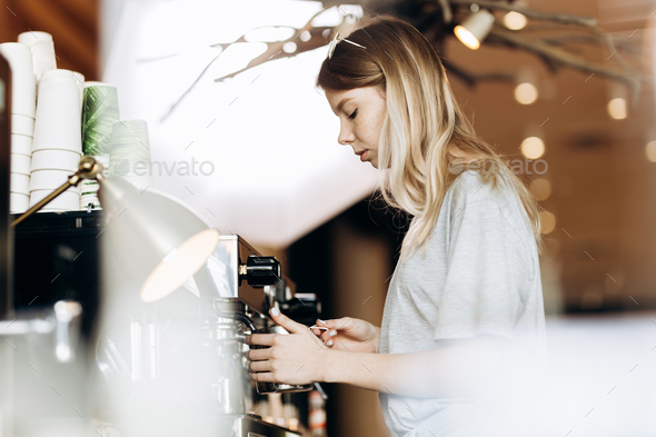 A good looking slim blonde with long hair,dressed in casual outfit,is cooking coffee in a modern - Stock Photo - Images