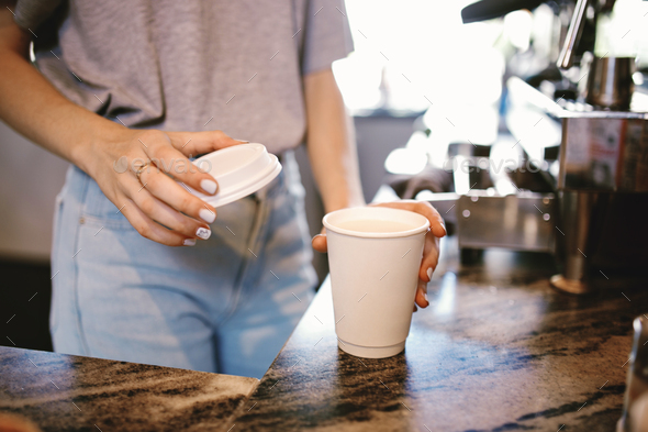 A slim young beautiful girl,dressed in casual outfit, gently puts the lid on the coffeein a cozy - Stock Photo - Images