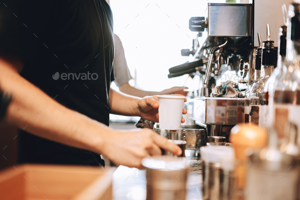 A young stylish man,wearing casual outfit,cooks coffee in a modern coffee shop. Hands and cups are - Stock Photo - Images