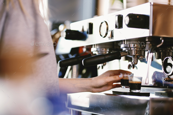 A young pretty blonde,wearing casual outfit,takes a cup of fresh coffee from an expensive coffee - Stock Photo - Images