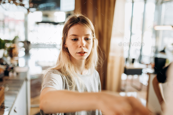 A friendly young slim girl with blonde long hair,wearing casual style,passes a coffee in a cozy - Stock Photo - Images