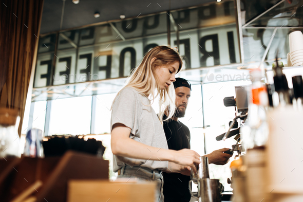 Two young baristas,a blonde girl and stylish man with beard,are shown cooking coffee together in a - Stock Photo - Images