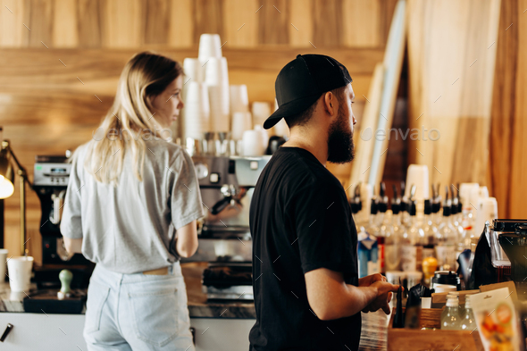 Two young stylish people,a thin blonde girl and a man with beard,wearing casual clotes,cook coffee - Stock Photo - Images