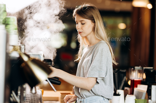 A youthful blonde slim gir,dressed in casual outfit,cleans the coffee machine with steam in a modern - Stock Photo - Images