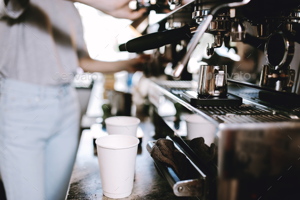 The process of cooking coffee is shown. Two glasses are standing next to a coffee machine, while - Stock Photo - Images