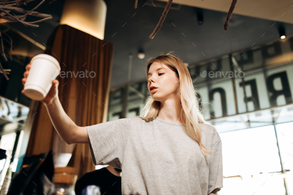 A youthful cute blonde girl,dressed in casual outfit,stands and holds a glass of coffee in a cozy - Stock Photo - Images