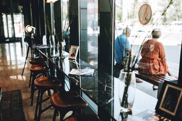 Tables with chairs are shown,situated next to a glass wall. Lovely atmosphere of the coffee shop is - Stock Photo - Images