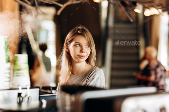 A smiling cute youthful blonde,dressed in casual clothes, stands next to the coffee machine and - Stock Photo - Images