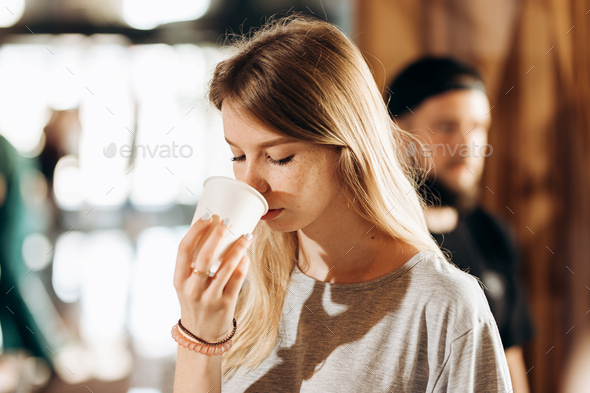 A good looking slim blonde girl,dressed in casual style,holds a cup of coffee and smells it in a - Stock Photo - Images