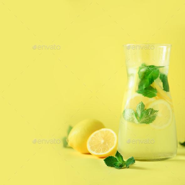 Citrus lemonade - mint, lemon and tropical monstera leaves on yellow background. Square crop. Detox - Stock Photo - Images