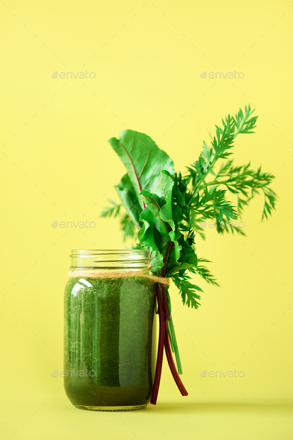 Smoothie with beet greens and carrot tops on yellow background, copy space. Summer vegan food - Stock Photo - Images