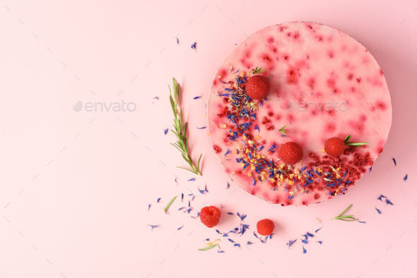 Delicious raspberry cake with fresh berries, rosemary and dry flowers on pink background. Copy space - Stock Photo - Images