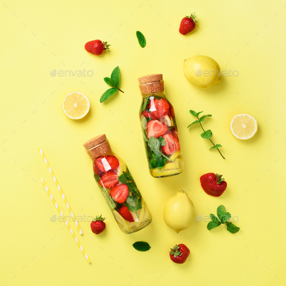 Bottle of detox water with mint, lemon, strawberry on yellow background. Square crop. Flat lay - Stock Photo - Images