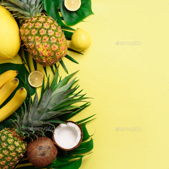 Exotic pineapples, coconuts, banana, melon, lemon, palm and monstera leaves on yellow, violet - Stock Photo - Images