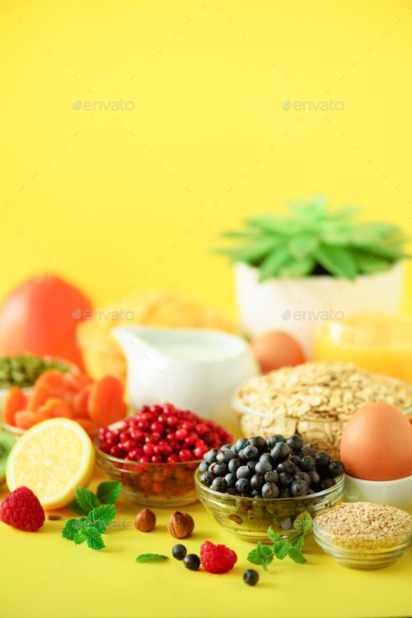 Vegan breakfast. Soft boiled egg, oat flakes, nuts, fruits, berries, milk, yogurt, orange, banana - Stock Photo - Images