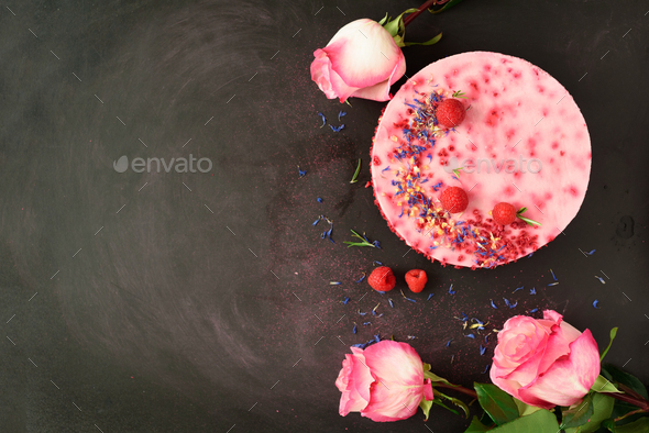 Pink roses and delicious raspberry cake with fresh berries, rosemary, dry flowers on dark vintage - Stock Photo - Images