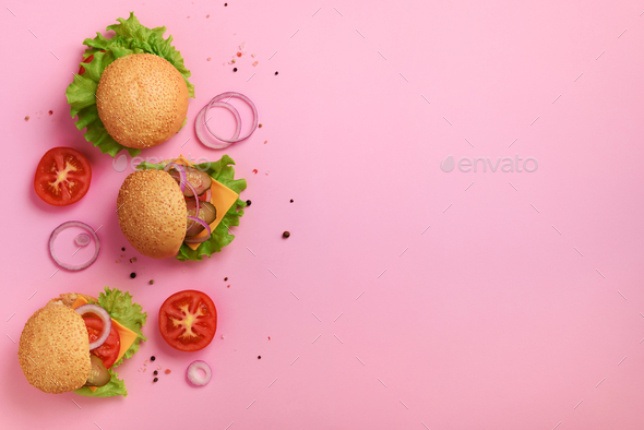 Delicious burgers, cheese, lettuce, onion, tomatoes on pink background. Close up banner. Unhealthy - Stock Photo - Images