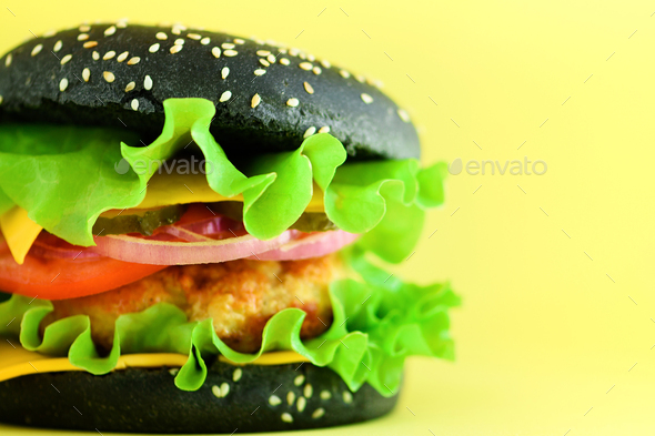 Macro view of tasty black burger with beef, cheese, lettuce, onion, tomatoes on yellow background - Stock Photo - Images