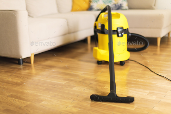 Woman in protective gloves cleaning the living room with yellow vacuum cleaner. Copy space. Clean - Stock Photo - Images