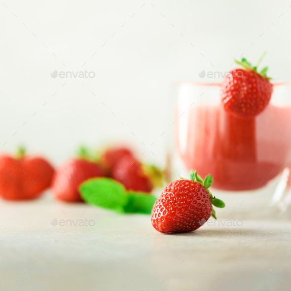 Bottle with vegan strawberry smoothie on grey background with copy space. Square crop. Summer food - Stock Photo - Images