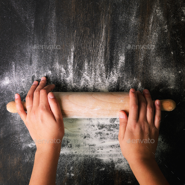 Girl hands keep rolling pin with flour on dark black table, baking background, top view, copy space - Stock Photo - Images