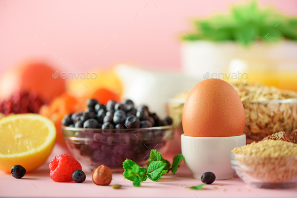 Delicious breakfast ingredients. Soft boiled egg, oat flakes, nuts, fruits, berries, milk, yogurt - Stock Photo - Images