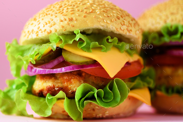 Macro view of tasty burger with beef, cheese, lettuce, onion, tomatoes on yellow background. Close - Stock Photo - Images