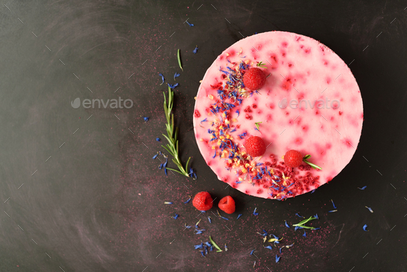 Delicious raspberry cake with fresh berries, rosemary and dry flowers on dark vintage background - Stock Photo - Images