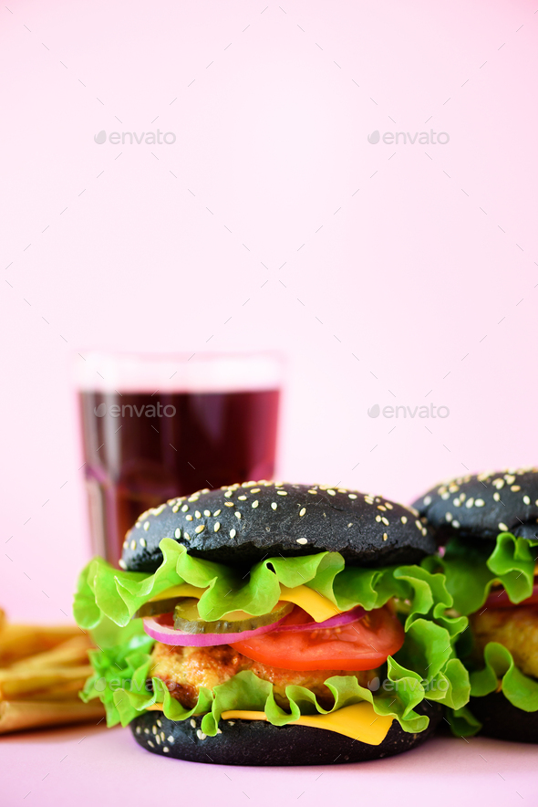Tasty black burgers or hamburger served with french fries on pink background. Copy space. Fast food - Stock Photo - Images