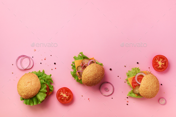 Tasty burgers with beef, tomato, cheese, onion, cucumber and lettuce on pink background. Top view - Stock Photo - Images