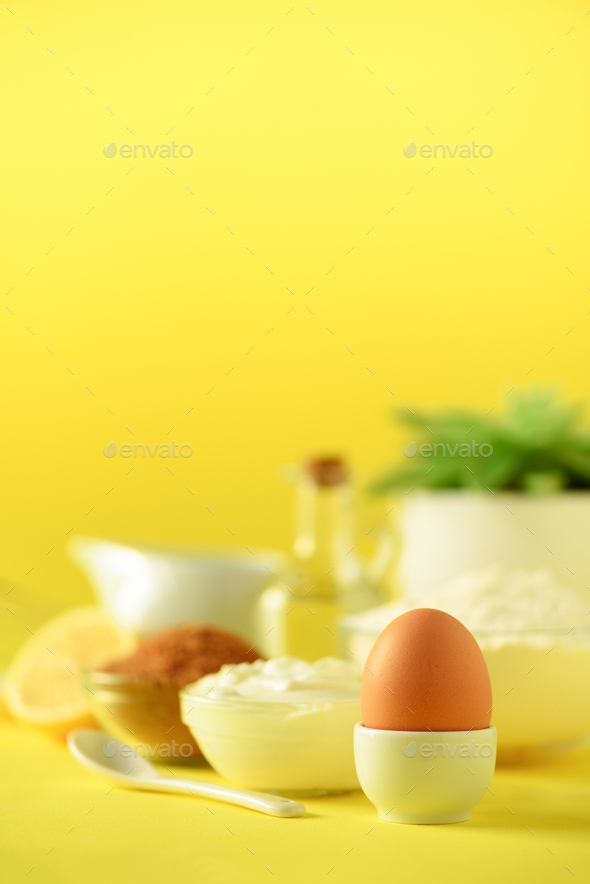 White cooking utensils on yellow background. Food ingredients. Macro of egg. Cooking cakes and - Stock Photo - Images