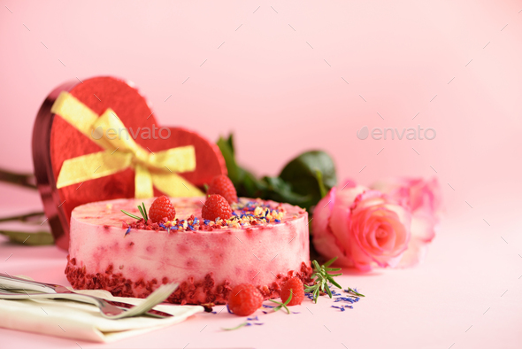 Gift boxes in shape of heart, roses, raspberry cake with fresh berries, rosemary and dry flowers on - Stock Photo - Images