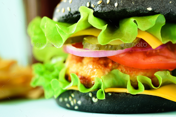 Macro view of tasty black burger with beef, cheese, lettuce, onion, tomatoes on blue background - Stock Photo - Images