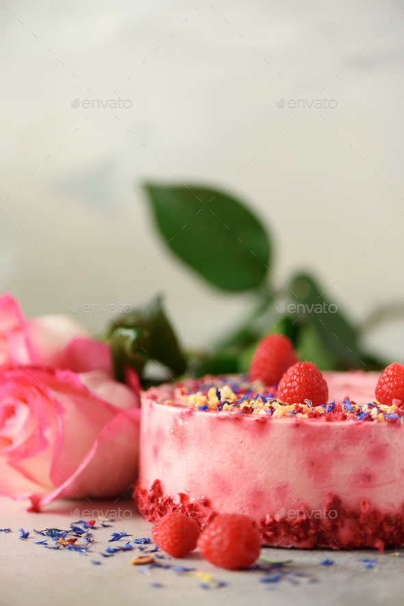 Pink roses and raspberry cake with fresh berries, rosemary, dry flowers on concrete background. Copy - Stock Photo - Images