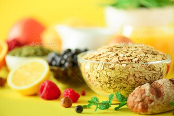Oat flakes with milk, fresh berries, yogurt, boiled egg, nuts, fruits, orange, banana, peach for - Stock Photo - Images