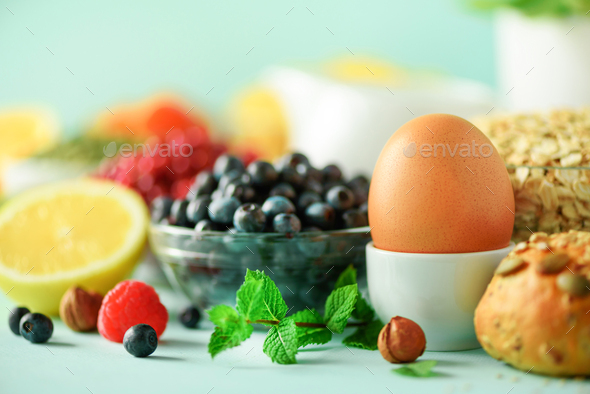 Breakfast served with soft boiled egg, oat flakes, nuts, fruits, berries, milk, yogurt, orange - Stock Photo - Images