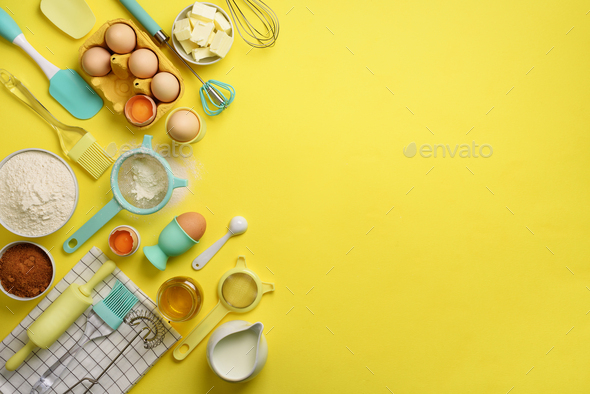 Butter, sugar, flour, eggs, oil, spoon, rolling pin, brush, whisk, towel over yellow background - Stock Photo - Images