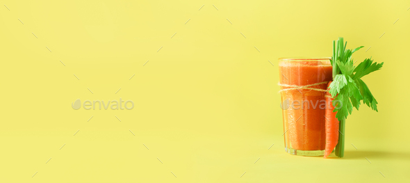 Fresh organic carrot juice with carrots, celery on yellow background. Vegetable smothie in glass - Stock Photo - Images
