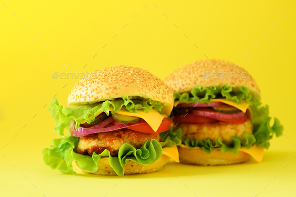 Fast food - juicy hamburger, french fries potatoes and cola drink on yellow background. Take away - Stock Photo - Images