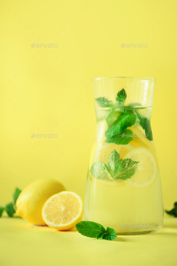Fresh summer fruits water or lemonade with mint, ice, lemon on yellow background. Copy space. Summer - Stock Photo - Images