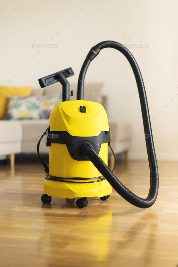 Yellow modern vacuum cleaner in living room. Copy space. Flat clean vacuuming concept - Stock Photo - Images