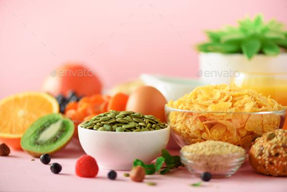 Corn flakes with milk, pumpkin seeds, fresh berries, yogurt, boiled egg, nuts, fruits, orange - Stock Photo - Images
