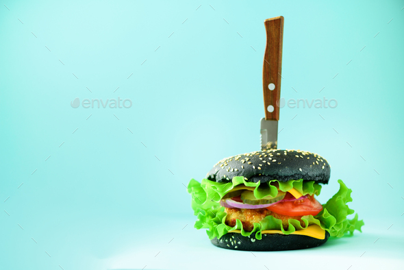 Fast food concept. Juicy black burger with knife on blue background. Take away meal. Unhealthy diet - Stock Photo - Images