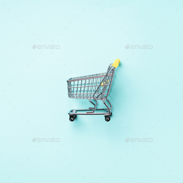 Shopping cart on blue background. Minimalism style. Square crop. Creative design. Top view with copy - Stock Photo - Images