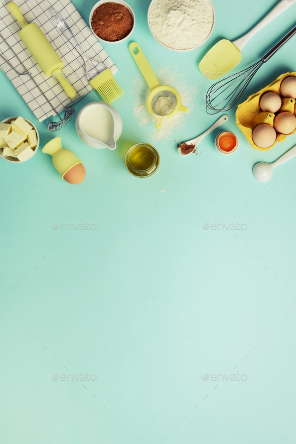 Baking ingredients - butter, sugar, flour, eggs, oil, spoon, rolling pin, brush, whisk, towel over - Stock Photo - Images